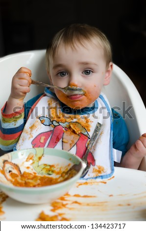 A very messy cute eight month old child trying to eat orange colored pasta - stock photo