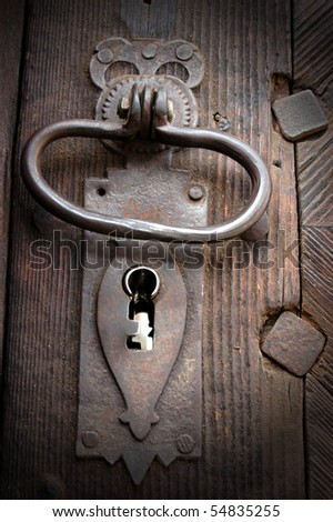 A very old door handle on a wooden door - stock photo