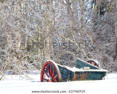 A very old rustic farm wagon half buried in a snowdrift. - stock photo