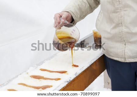A very old way of using heated maple syrup to make a treat from. - stock photo