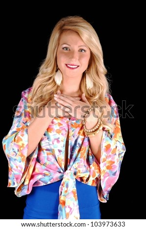 A very pretty young woman with long blond curly hair, in a colorful blouse holding her hands on her chest for black background. - stock photo