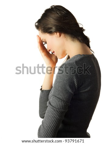 A very sad and depressed woman crying and hiding her face in her hands - stock photo
