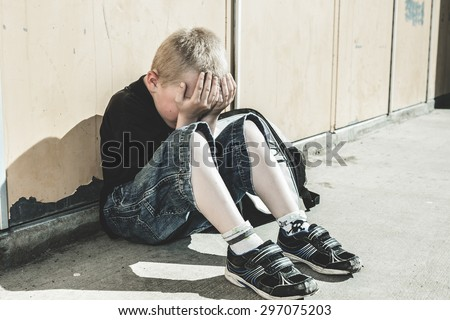 A very sad boy lay on the ground seam to be bullying in school playground. - stock photo