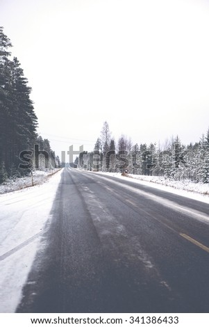 A very slippery road during winter. Black ice is covering the whole road and it is dangerous to drive even with studded winter tires. Image has a vintage effect applied. - stock photo