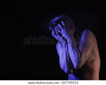 A very stressed or depressed man covers his face with his hands.  - stock photo