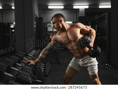 A very strong young guy bodybuilder, doing exercises with dumbbells in the gym. Fitness muscular body on dark background - stock photo