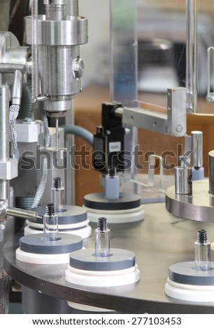 A vial filling machine in a cosmetics factory. - stock photo
