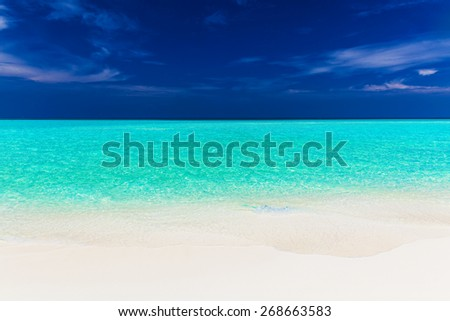 A vibrant shot of clear empty beautiful tropical beach with blue sky - stock photo