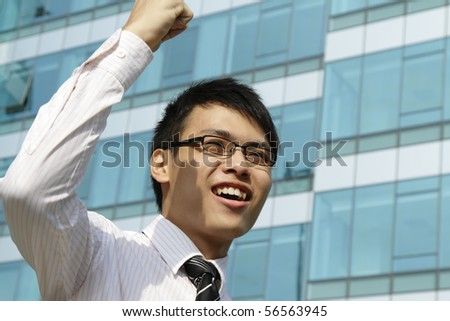A victorious executive waving his fist - stock photo