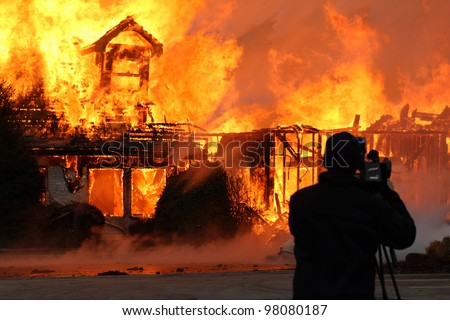 A videographer braving heat of a blazing fire that devoured what once was a two story wood framed building makes for a dramatic photograph. - stock photo
