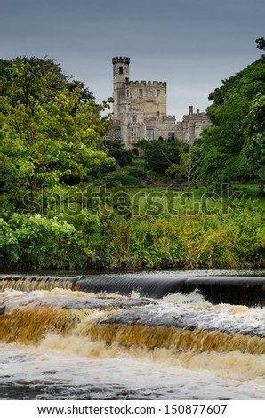 A view across the weir to Hornby Castle in the distance with the Wenning River in the foreground. Lancashire, England - stock photo