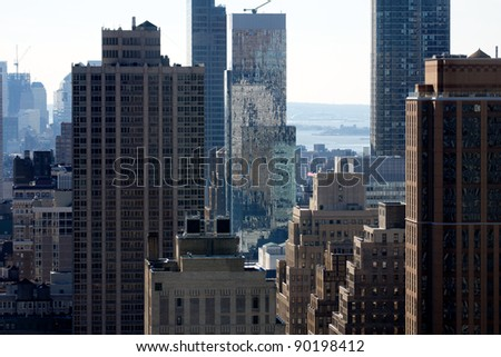 A view among Manhattan's chaotic jumble of Skyscrapers and lower buildings, with Ellis Island in the distance. - stock photo