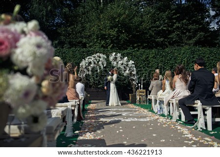 A view from afar on a wedding couple kissing in the front of an altar - stock photo