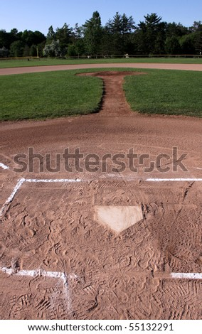 A view from behind home plate of an unoccupied baseball field. - stock photo