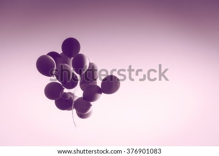 A view from below of a group of balloons flying in the air. - stock photo