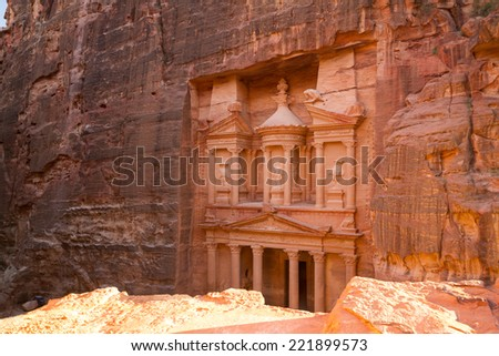 A view from the top of the opposite cliff on the magnificent facade of the Treasury in Petra, Jordan, carved in the stone of the mountain. - stock photo