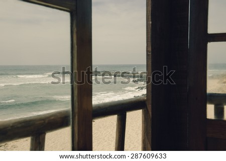 A view from the wooden terrace through the opened window on ocean beach. Algarve, Portugal. Selective focus on the landscape. Aged toned photo. - stock photo