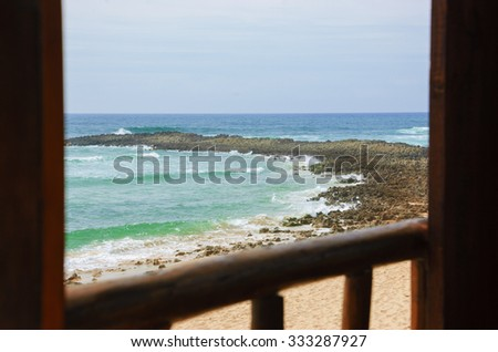 A view from the wooden terrace through the opened window on ocean beach. Algarve, Portugal. Selective focus on the landscape. - stock photo