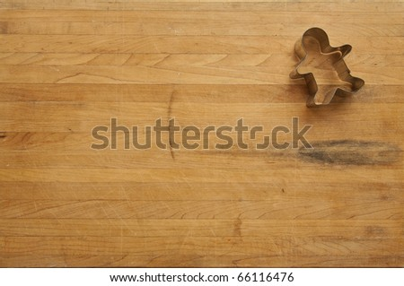 A view looking down on a single metal gingerbread man cookie cutter on a worn butcher block cutting board - stock photo