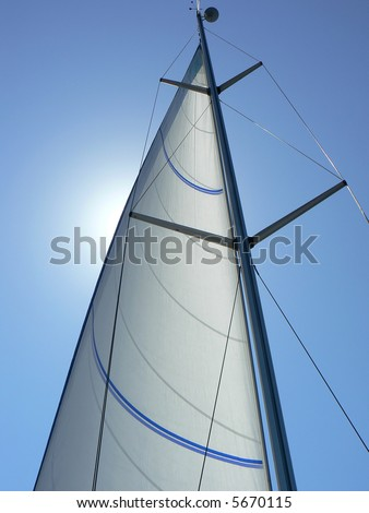 A view looking upwards at the mast, sail and rigging of a private yacht underway. Vertical perspective. - stock photo