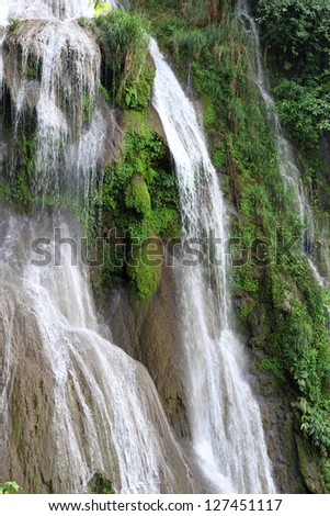 A view of a beautiful waterfall flowing over tropical vegetation - stock photo