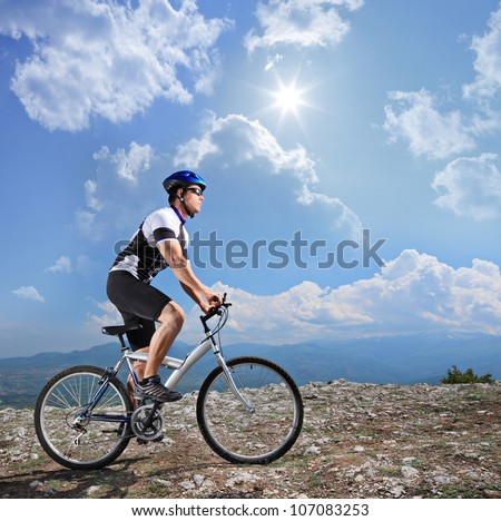 A view of a biker riding a mountain bike on a sunny day, Macedonia - stock photo
