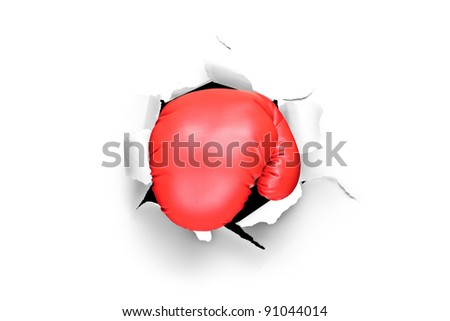 A view of a boxing glove through a hole in paper - stock photo