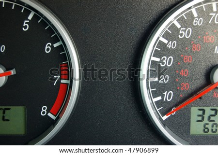 A view of a car instrument panel showing speedometer and rev counter - stock photo