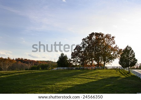 A view of a field at sunset in the fall. - stock photo