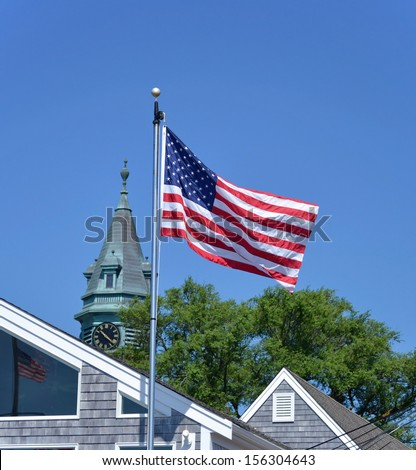 A view of a flag and the town hall spire in Provincetown, Massachusetts - stock photo