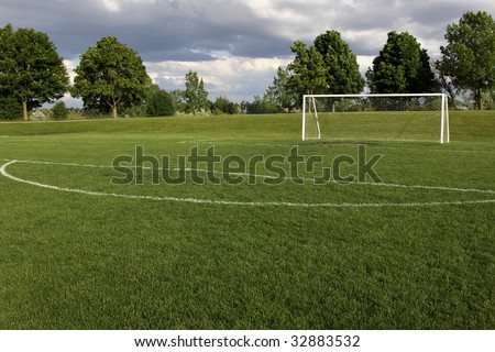 A view of a net on a vacant soccer pitch. - stock photo
