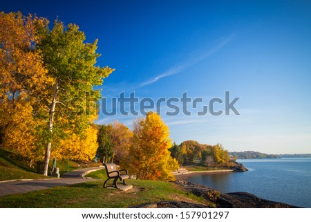 A view of a park and lake during autumn season - stock photo