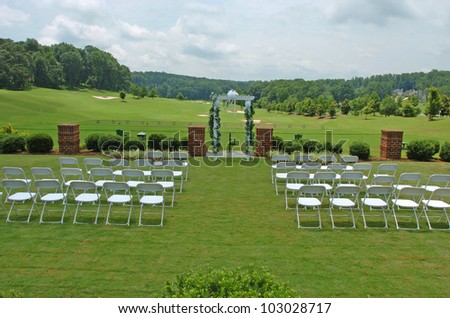 A view of a wedding setup with chairs and floral arch before wedding - stock photo