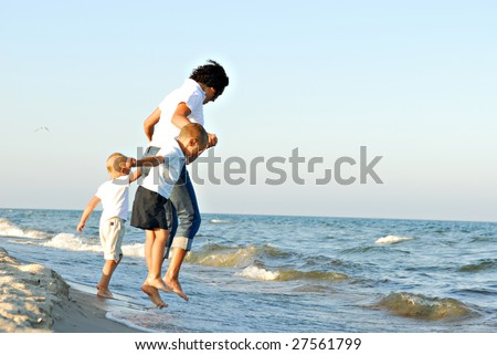 A view of a young woman and two young boys holding hands and jumping on a beach as waves and surf reach the shore. - stock photo
