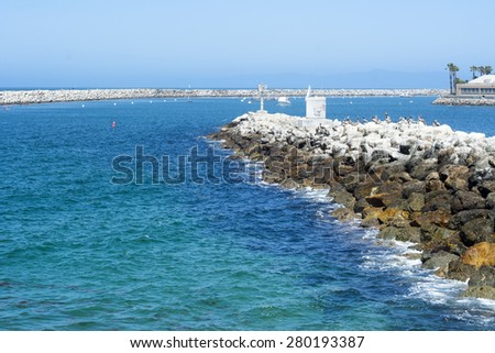 A view of King Harbor breakwater during a bright, sunny day reveals the shallow, turquoise water surrounding the bay. - stock photo