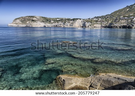 A view of Sant'Angelo in Ischia island in Italy: Tyrrhenian sea, rocks,  clear crystal blue and green water, sand and old typical houses in the island in front of Naples in Campania in a sunny day - stock photo