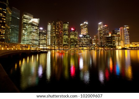 A view of Singapore business district Marina Bay in the night time with water reflections. - stock photo