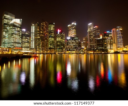 A view of Singapore business district Marina Bay, in the night time, with water reflections. - stock photo