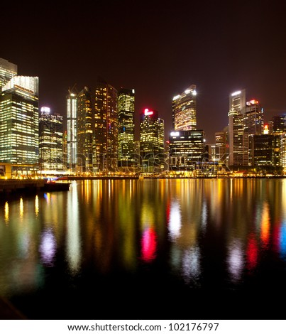 A view of Singapore business district, with water reflections. - stock photo