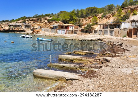 a view of the Cala Corral cove in Ibiza Island, Spain, with its traditional fishermen shelters - stock photo