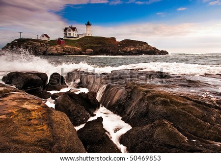 A view of the Cape Neddick lighthouse across the rocks showing the waves. - stock photo