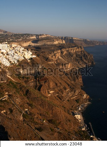 A view of the dark volcanic cliffs and Fira town on Santorini, Greece, at sunset. - stock photo
