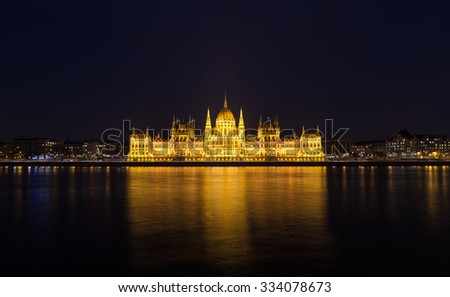 A view of the Hungarian Parliament building along the Danube River at night with the building lit up and reflections in the water. There is space for text. - stock photo