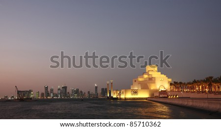 A view of the Museum of Islamic Art at night, with the Dafna district's high-rise skyline in the background. - stock photo