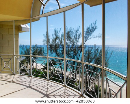 A view of the ocean through an glass window arch of a balcony. - stock photo