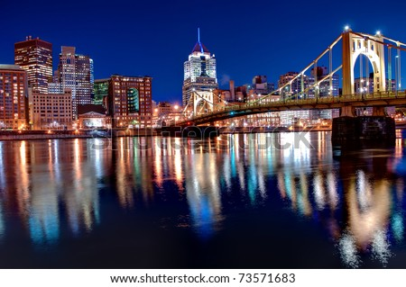 A view of the Pittsburgh, Pennsylvania cityscape at night overlooking the Allegheny River with views of the Roberto Clemente Bridge. - stock photo