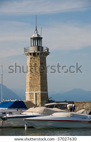 A view of the yachts and lighthouses on the bank of lake Garda, in Italy, on a sunny afternoon. - stock photo