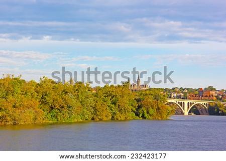 A view on Georgetown University across Potomac River in autumn. Fall colors of Potomac riverside and Key Bridge, Washington DC. - stock photo