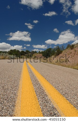 A view shot from the middle of an old western road in the middle of nowhere. - stock photo