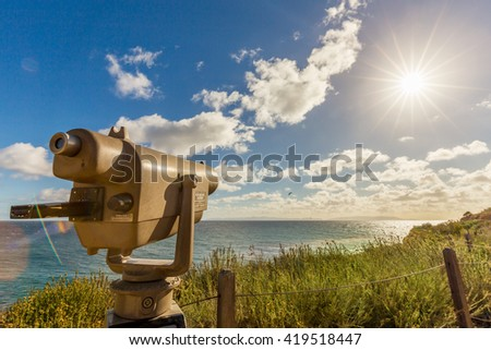 A viewing telescope catches a view of the sun over the ocean and an island. - stock photo
